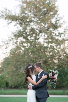 bride in simple bhldn dress and alfred angelo headpiece hugs groom in bhldn, foreheads touch