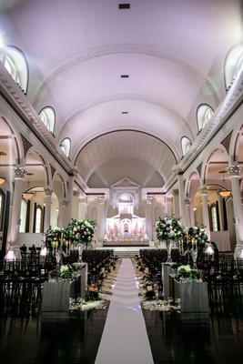 Vibiana wedding ceremony with white aisle runner greenery and burgundy flower arrangements altar