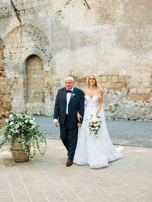 bride in sweetheart neckline strapless wedding dress neutral bouquet with father of bride stone wall