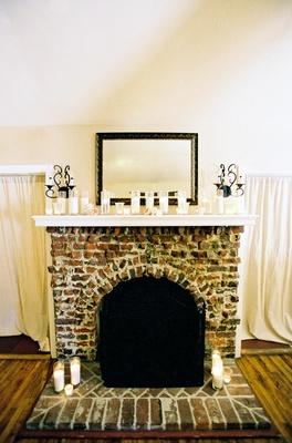 Brick fireplace with a row of candles on mantle