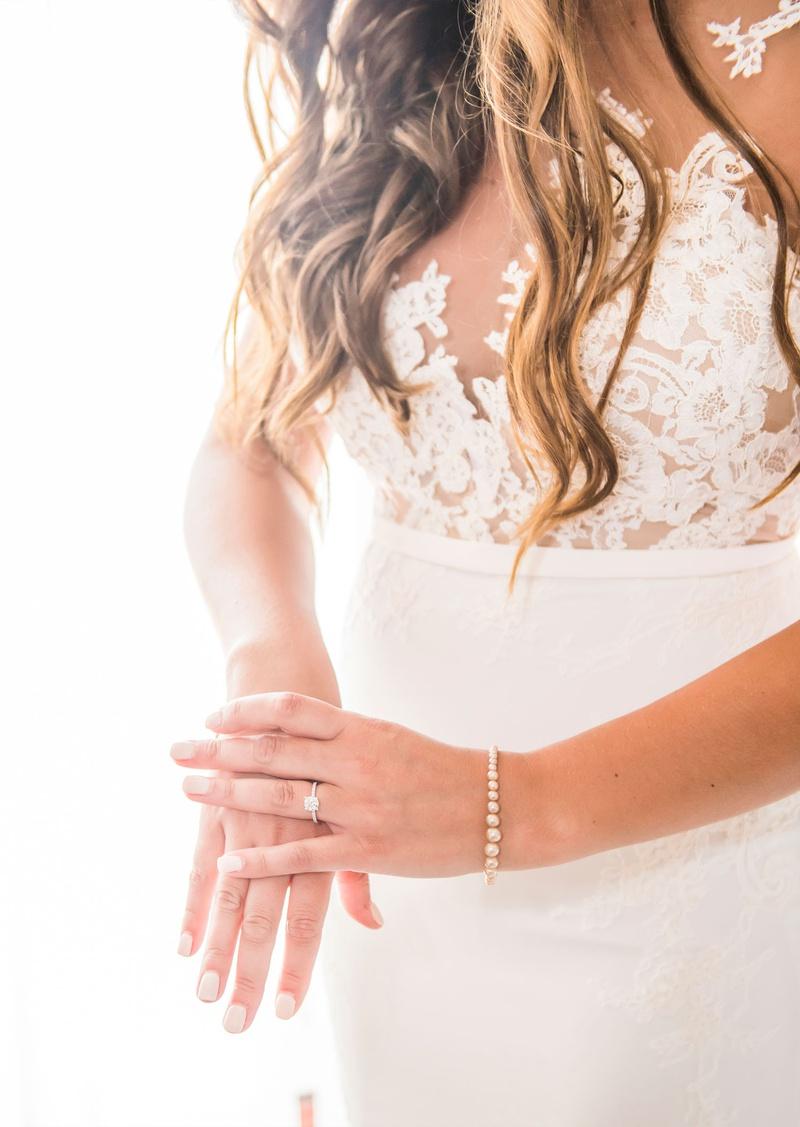 bride in crepe pronovias wedding dress with illusion bodice nude manicure nails pearl bracelet