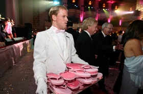 White glove waiter with pink flip flops on tray