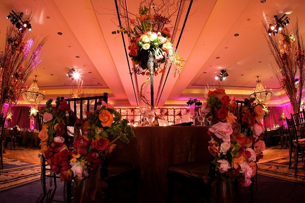 Sweetheart table with chairs covered in flowers