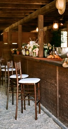 Barstools at rustic country bar for barn wedding