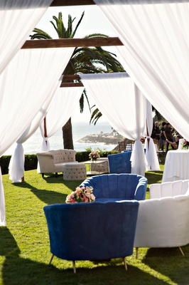 wedding reception with view of beach and ocean green lawn tufted furniture grey blue white lounge