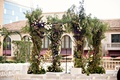 chuppah with lush greenery and lavender and violet flowers