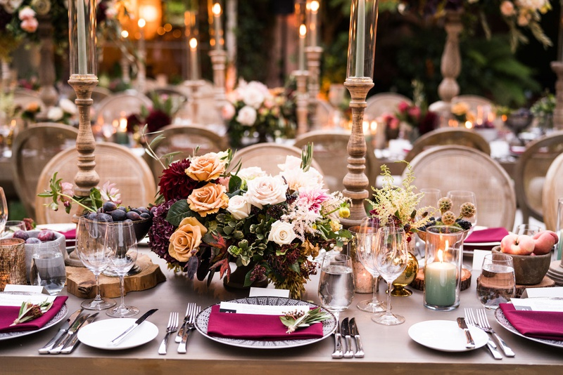 wedding reception table wood with burgundy flowers napkins candles taper candles outdoor wedding