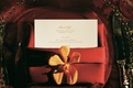 Red wedding place setting with menu and orange orchid