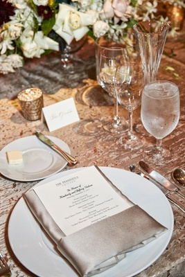 silver tablescape with linens and napkin and reception menu on plate