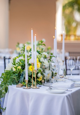wedding reception sweetheart table taper candle gold candleholder greenery white yellow flowers