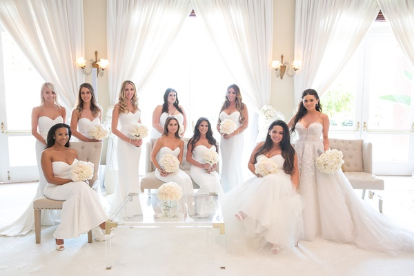 bride in inbal dror wedding dress with zuhair murad overskirt, bridesmaids in white runway dresses
