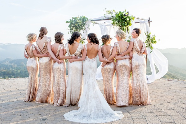 Bride in low back Monique Lhuillier wedding dress and bridesmaids in sequin cowl back dresses