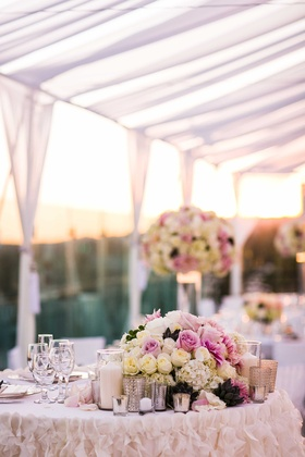 Bride and groom's sweetheart table with ruffle linen and low centerpiece of pink and white roses