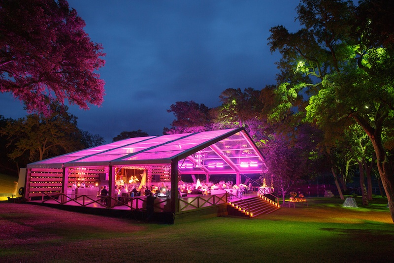 Outdoor Wedding Reception Wood Structure With Open Side And Clear Ceiling Is Lit By Fuchsia Lighting