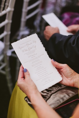 White ceremony booklet with gold lettering