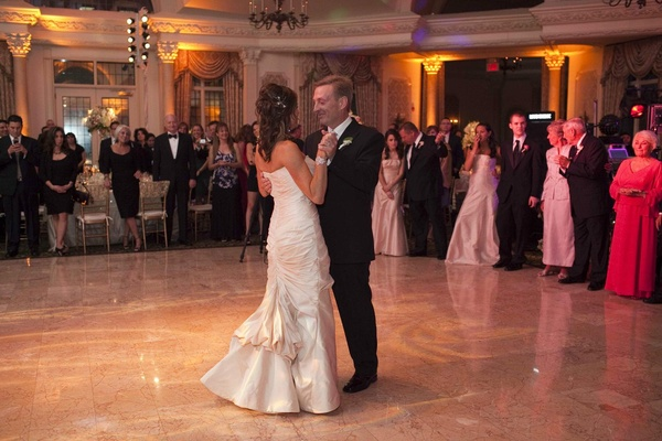 Bride in a Romona Keveza dress dances with groom in a black tuxedo