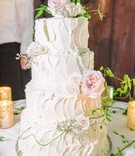 four layer wedding cake white classic design stucco style pink garden rose greenery vines