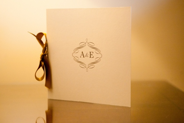 White ceremony program with gold monogram