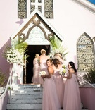 Bridesmaids in light pink blush bridesmaid dresses walking up stairs into light pink church Bahamas