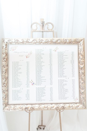 wedding reception seating chart with flower motif print silver frame on easel drapery
