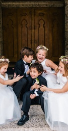 flower girls white dresses with flower crowns, ring bearers in tuxes laughing
