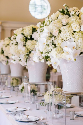 White wedding reception decor, white hydrangea, orchid, rose centerpiece in ginger jar on lucite