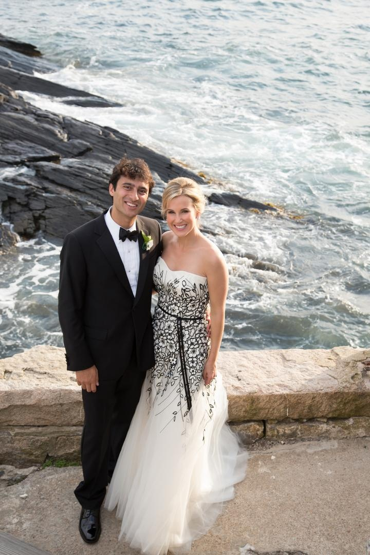 Bride and groom on stone cliff above ocean