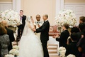 Bride and groom at altar of church with white and blush wedding flower decorations