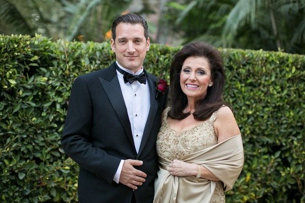 Mother of the groom wearing sleeveless champagne beaded evening gown with tan wrap with groom in tux