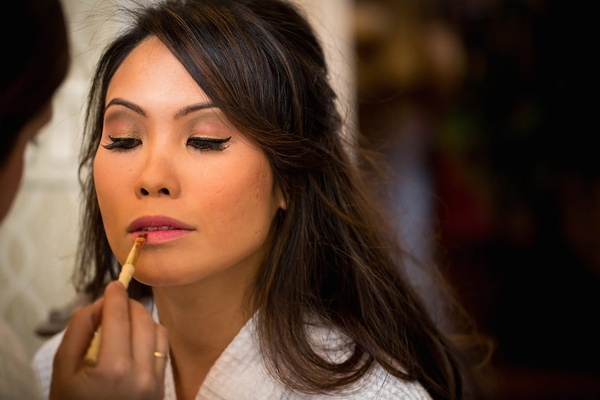 Makeup artist finishes bride's look with light pink lipstick