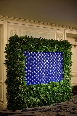 Escort card display glass ornaments on blue background framed with green leaves greenery hedge wall