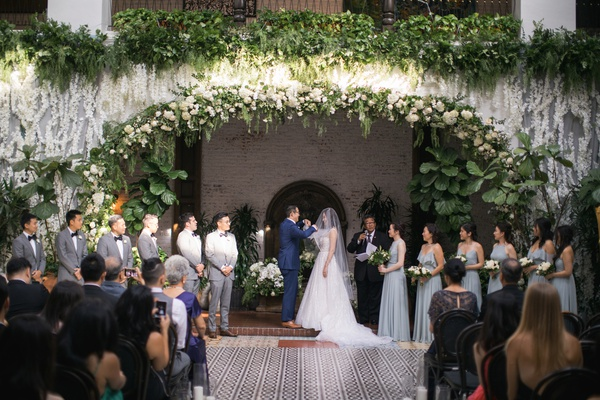 ebell long beach wedding ceremony with orchids and greenery from balcony with bridal party under