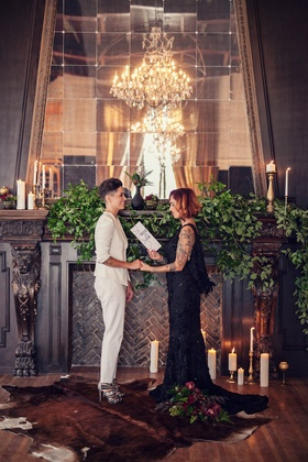 Wedding ceremony with a bride wearing white blazer, pants with bride in a black R-Mine Bespoke dress