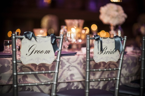 Silver chairs with die-cut Bride and Groom chair signs tied with satin ribbon