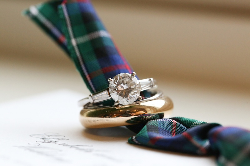 Gold men's wedding band and round cut diamond engagement ring with side stones on plaid invitation