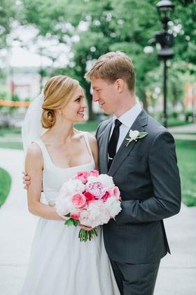 blonde bride with low chignon bun, groom in grey suit with arm around bride, peony bouquet