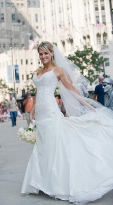 Bride in a veil and gown with a thin strapped beaded bodice and full skirt