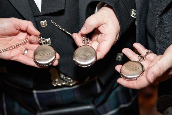 Groom & groomsmen in black blazers show metal pocket watches with monograms in green