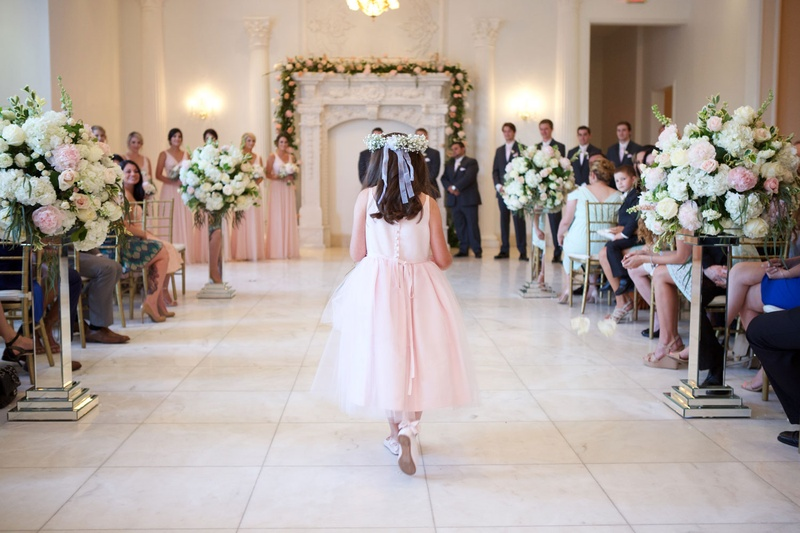 Back of flower girl walking down aisle with ribbon in hair and ribbons on pink shoes