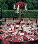 round table with red linens and black chairs