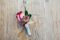 red white and purple boutonniere with rose and leaves sits on top of wooden table with hearts carved