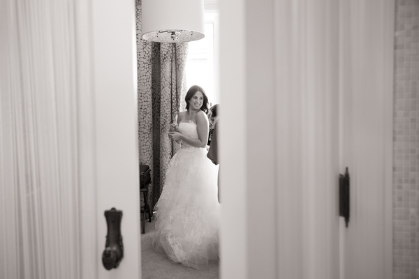 black and white photo of bride preparing for her wedding and wearing her dress
