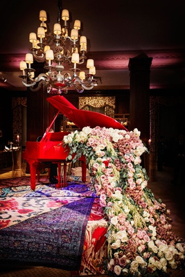 unique wedding decor red grand piano overflowing with pink white roses and greenery layered rugs