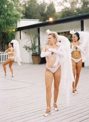 Women in bras and underwear with unique feather headpieces during cabaret show at wedding reception