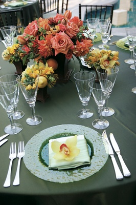 Green table with yellow and orange flower centerpieces