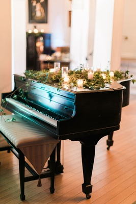 Wedding ceremony downtown los angeles grand piano with candles and greenery on top decorations