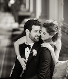 Black and white photo of bride in Anne Barge dress and groom in tuxedo and bow tie arm draped over