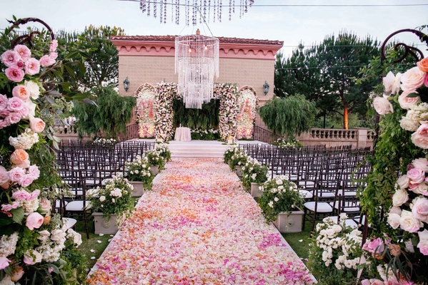 Alfresco jewish wedding ceremony lush reception in san diego flower petal aisle pink orange rose bush decorations flowers on wrought iron gate chandelier junglespirit Gallery