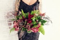 Bride in a black gown with appliques, beading carries bouquet of greenery, red roses, orchids,