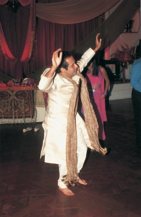 Groom dances at Indian wedding reception